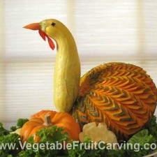 Thanksgiving centerpiece made of carved kabocha squash made to look like a turkey, close up detail of kaboch squash carving- turkey feather details