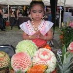 Thai girl in traditional costume with fruit carvings.