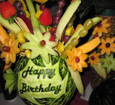 Happy Birthday watermelon carving used as a vase for a lovely fruit bouquet.