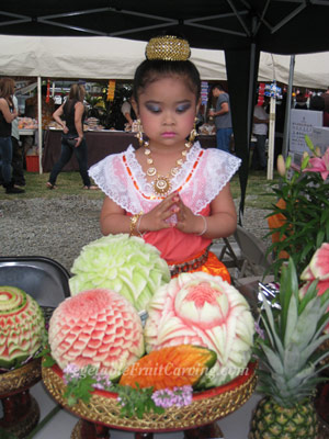 girl in tradition dress and fruit carvings at Songran Festival