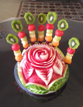 "carved watermelon ""cake"" with skewered fruit ""candles""."
