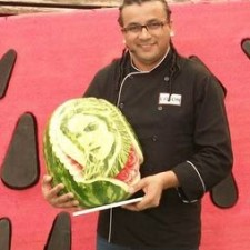 Fruit Carver Edson Oliveira with one of his watermelon portraits