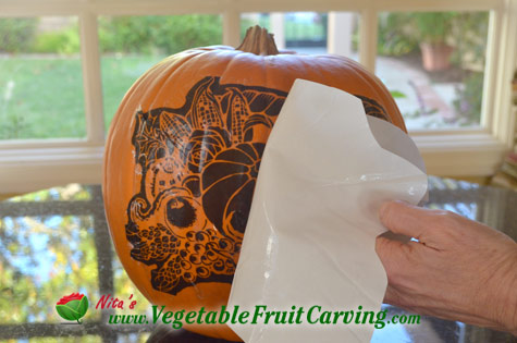 Peeling off tranfer paper from pumpkin