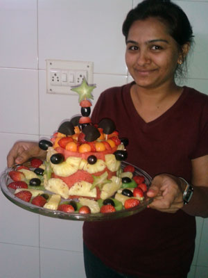 Mona Bhavsar shows off her watemelon cake an fruit tray. I like how she tops the cake with a slice of skewered star fruit. It's fun.
