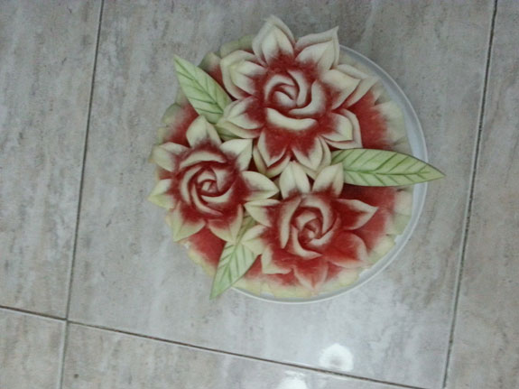 Top view of Saada's cake topped with carved watermelon flowers. the leaves are carved from the pieces of the inside rind.