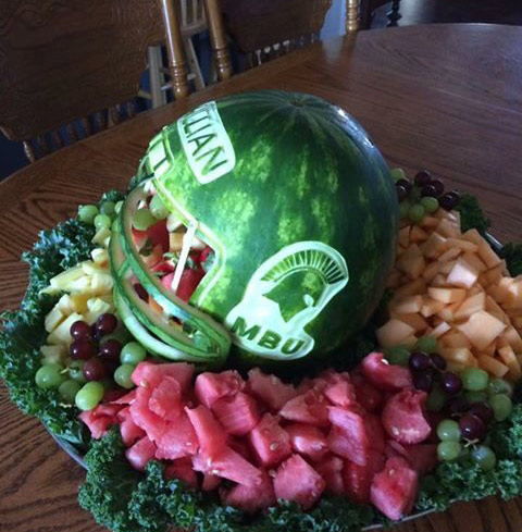 Trojan logo carved on watermelon football helmet