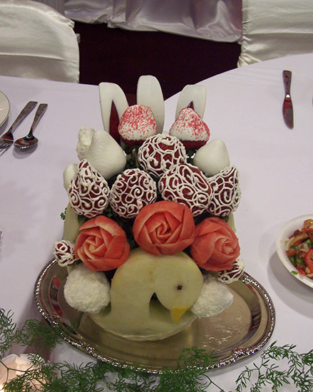 honeydew melon swan with chocolate strawberries.